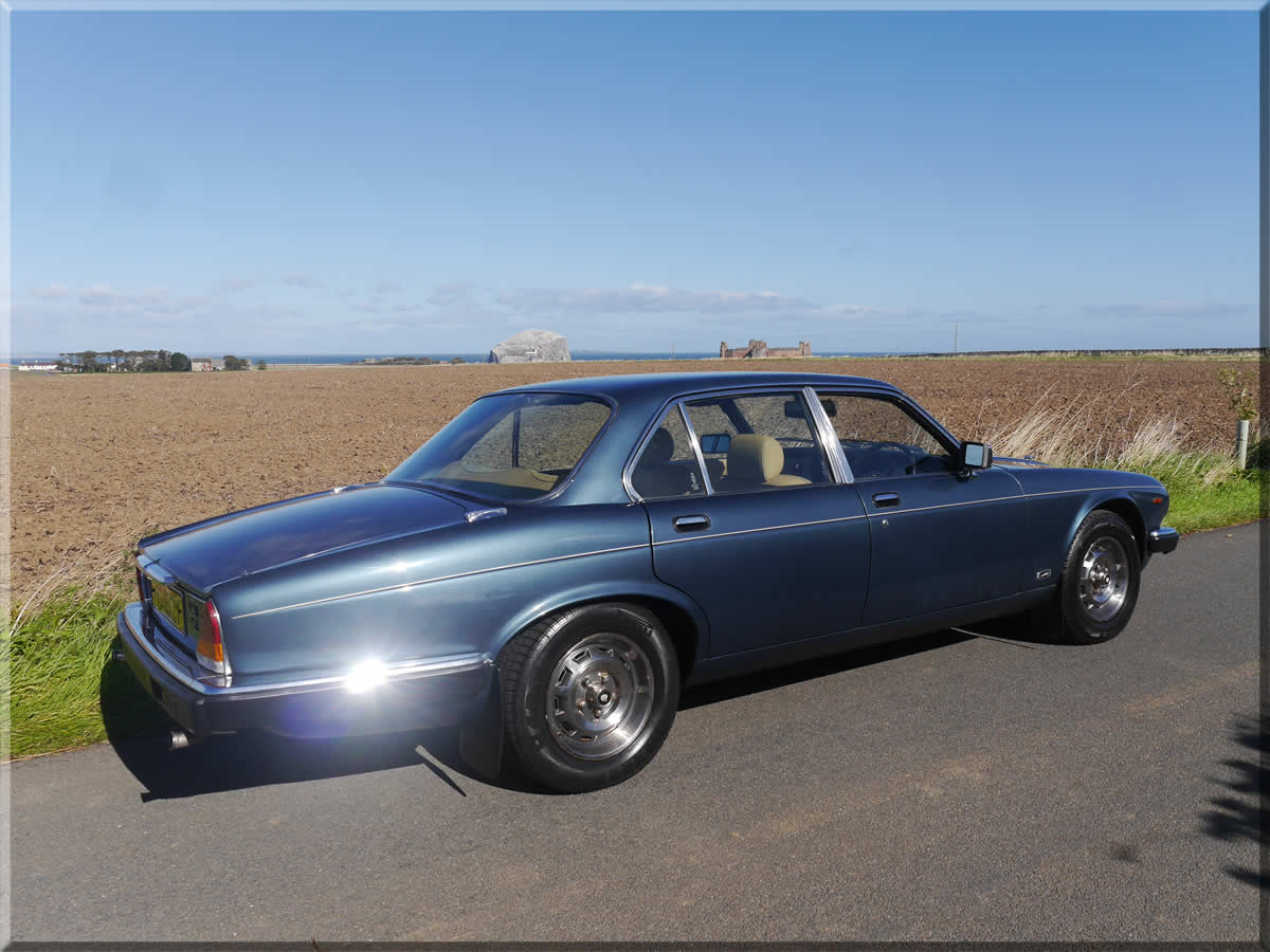 Jaguar XJ6 side view with Bass Rock in background